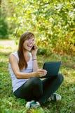 Mujer joven con la computadora portátil y hablar Fotografía de archivo libre de regalías