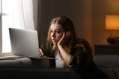 Mujer joven con la computadora port?til en el sof? Concepto de la soledad fotos de archivo libres de regalías