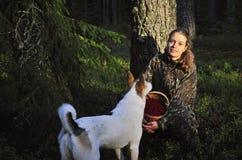 Mujer joven con la cosecha Cowberrys del perro. Imagen de archivo libre de regalías