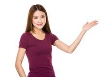 Mujer joven con la demostración de la mano con la muestra en blanco Imagenes de archivo