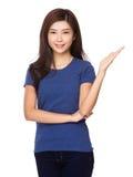 Mujer joven con la demostración de la mano con la muestra en blanco Imagen de archivo