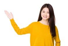 Mujer joven con la demostración de la mano con la muestra en blanco Foto de archivo