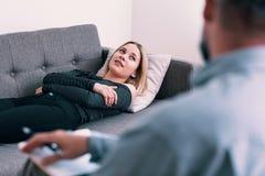 Mujer joven con la depresión que escucha un psicoterapeuta fotos de archivo libres de regalías