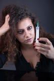 Mujer joven con la drogadicción en el fondo oscuro, jeringuilla en las FO Foto de archivo