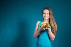 Mujer joven con la ensalada fresca en fondo azul. fotos de archivo