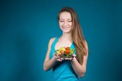 Mujer joven con la ensalada fresca en fondo azul. foto de archivo libre de regalías