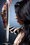 Mujer joven con la espada del samurai Foto de archivo