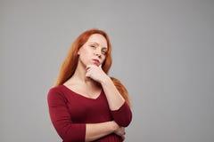 Mujer joven con la expresión facial pensativa que lleva a cabo h Fotos de archivo libres de regalías