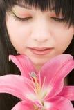 Mujer joven con la flor del lirio Imagen de archivo