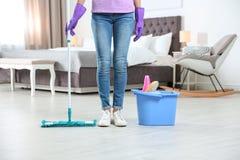 Mujer joven con la fregona y detergentes en dormitorio servicio de la limpieza imágenes de archivo libres de regalías