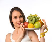 Mujer joven con la fruta fresca y la cinta métrica imagen de archivo