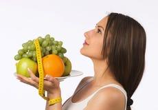 Mujer joven con la fruta fresca y la cinta métrica foto de archivo libre de regalías