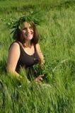 Mujer joven con la guirnalda de la hierba en su cabeza Foto de archivo libre de regalías