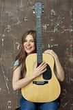 Mujer joven con la guitarra acústica Imagen de archivo