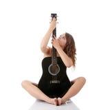Mujer joven con la guitarra clásica negra Imágenes de archivo libres de regalías
