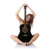 Mujer joven con la guitarra clásica negra Foto de archivo