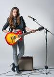 Mujer joven con la guitarra en su mano Fotos de archivo