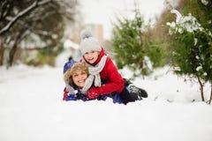 Mujer joven con la hija de la mentira de la edad de escuela que abraza en nieve Fotografía de archivo