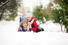 Mujer joven con la hija de la mentira de la edad de escuela que abraza en nieve Foto de archivo libre de regalías