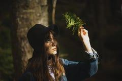 Mujer joven con la hoja del helecho en el bosque verde Foto de archivo