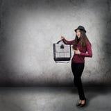 Mujer joven con la jaula de pájaro Imagenes de archivo