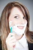 Mujer joven con la máquina de afeitar en su cara fotos de archivo libres de regalías