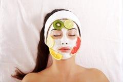 Mujer joven con la máscara de la fruta en una cara fotografía de archivo
