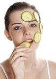 Mujer joven con la máscara de la rebanada de un pepino Imagen de archivo