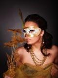 Mujer joven con la máscara en fondo gris. Fotografía de archivo