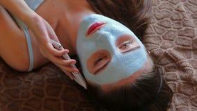 Mujer joven con la máscara facial metrajes