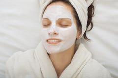 Mujer joven con la máscara facial del krem Imágenes de archivo libres de regalías