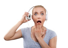 Mujer joven con la música que escucha de los auriculares, chocado, aislada Fotos de archivo