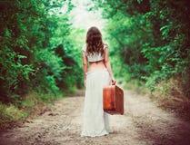 Mujer joven con la maleta a disposición que sale por el camino rural Imagenes de archivo