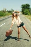 Mujer joven con la maleta que hace autostop a lo largo de un camino Fotografía de archivo libre de regalías