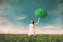 Mujer joven con la maleta y el paraguas Imagen de archivo