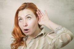 Mujer joven con la mano al oído que escucha Fotos de archivo