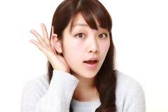 Mujer joven con la mano detrás del oído que escucha de cerca Imágenes de archivo libres de regalías