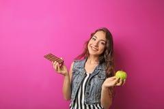 mujer joven con la manzana y el chocolate Imagen de archivo libre de regalías