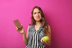 mujer joven con la manzana y el chocolate Fotos de archivo