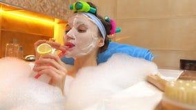Mujer joven con la mascarilla que tiene su bebida en bañera espumosa Tiempo de relajación vídeo 4K almacen de video