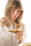 Mujer joven con la miel y el pan Fotos de archivo libres de regalías