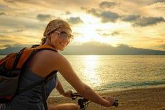 Mujer joven con la mochila colocando en la orilla cerca la suya la bici Fotografía de archivo