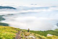 Mujer joven con la mochila en montañas Fotografía de archivo libre de regalías