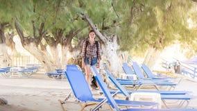 Mujer joven con la mochila en una playa Fotos de archivo libres de regalías