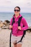 Mujer joven con la mochila en una playa Fotografía de archivo libre de regalías