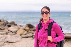Mujer joven con la mochila en una playa Imagen de archivo libre de regalías