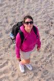 Mujer joven con la mochila en una playa Fotografía de archivo