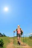 Mujer joven con la mochila que camina en el día soleado en la montaña Imagenes de archivo