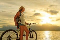 Mujer joven con la mochila que se coloca en la orilla cerca de su bici Fotos de archivo libres de regalías