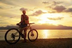 Mujer joven con la mochila que se coloca en la orilla cerca de su bicicleta Fotos de archivo